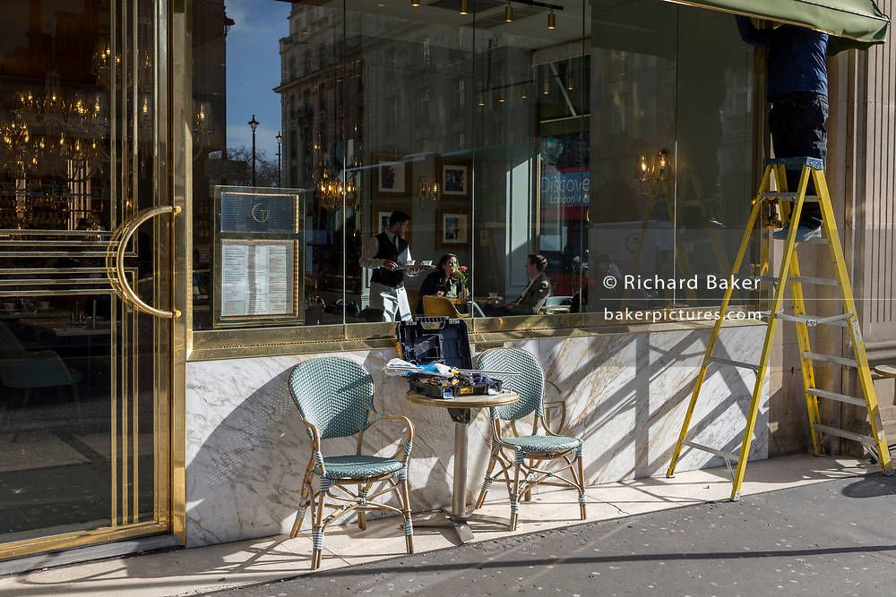 While a waiter serves customers sitting in winter sunlight, a workman stands on stepladders to repair the awning of Cafe Grand by Concerto on on the corner of Dover Street and Piccadilly, on 18th February 2020, in London, England.