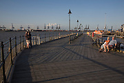 People enjoying afternoon sunshine Ha'penny pier Harwich, Essex, England