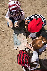 Directly above shot of children examining a treasure map in a adventure playground, Bavaria, Germany