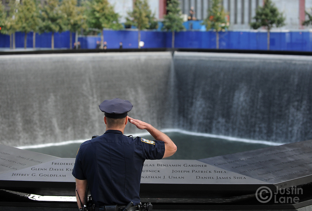A New York City police officer salutes at the North Pool of the 9/11 Memorial during the singing of the National Anthem during the tenth anniversary ceremonies at the site of the World Trade Center September 11, 2011, in New York. POOL/Justin Lane/EPA