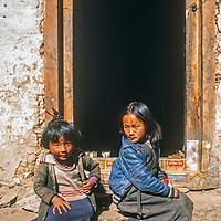 Sherpa children sit in a doorway in the Knumbu region of Nepal.
