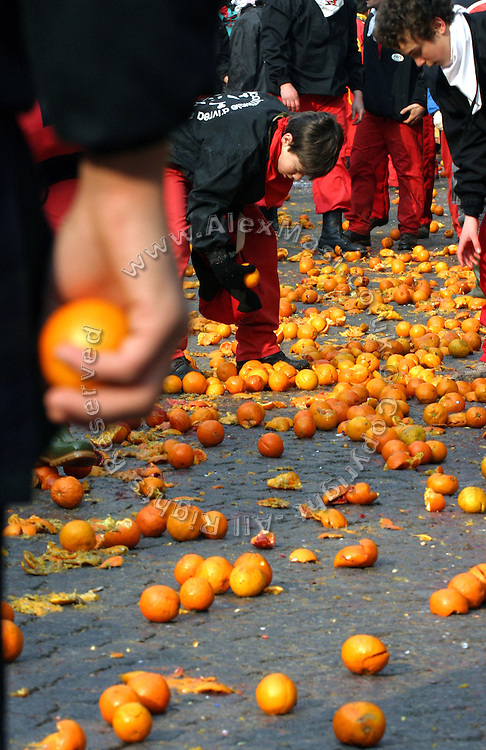 Throwers are collecting oranges to fight the next horse-van passing through their location in Ivrea, pop. 30.000. During the days of the Carnival, the town becomes crammed with tourists coming to witness the event which finds its roots at the end of the XII Century, when the people led an insurrection against the local tyrant, Count Ranieri of Biandrate, who was exercising the 'jus primae noctis' rule (having the first night) on the local young brides. The battle to overthrow him is represented with a 3-day-fight between factions in which more then 400 tonnes of oranges are thrown. During the celebrations, food stalls, bands playing music, and parades are also present, giving it a typical Medieval atmosphere. ...