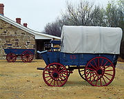 Wagons next to building housing, bakery, blacksmith and workshops, Fort Larned National Historic Site, Santa Fe Trail, Kansas.