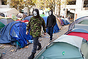 Masked protestors walk between the tents of Occupy London OSLX, St Pauls Catherdral, London.