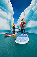 A couple on stand up paddle boards (SUP) explore an iceberg canyon on Bear Lake in Kenai Fjords National Park, Alaska.