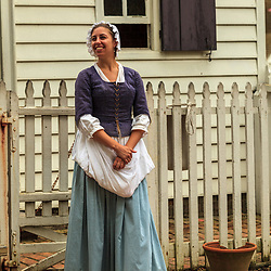 Costumed interpreter portrays a woman colonist at Colonial Williamsburg, VA.
