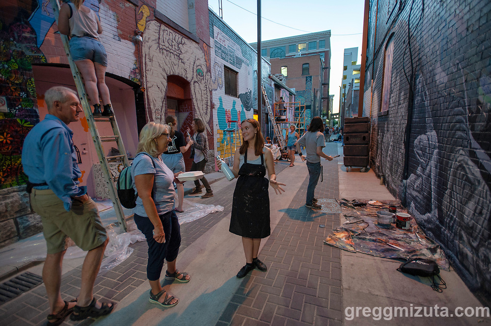 """Claire Harlow works on her mural during Freak Alley Gallery's eighth annual mural event in downtown Boise, Idaho on August 6, 2018. <br /> <br /> She just moved to Boise from Kansas City where she recently earned a BFA in illustration. This was her second mural in Freak alley but she was feeling pressure to make this good, being an event introducing her to the local creative community. <br /> <br /> Her subject was a play on Wile E. Coyote. In her original painting, the coyote faces the opposite direction than the coyote in her mural. Colby wanted it reversed so it was leading into the alley. She likes painting anything that is predatory with ears that stick up and a fluffy tail.<br /> <br /> Freak Alley Gallery's week long event provided an """"art-in-motion"""" experience as it welcomed the public to watch artists work on their murals."""