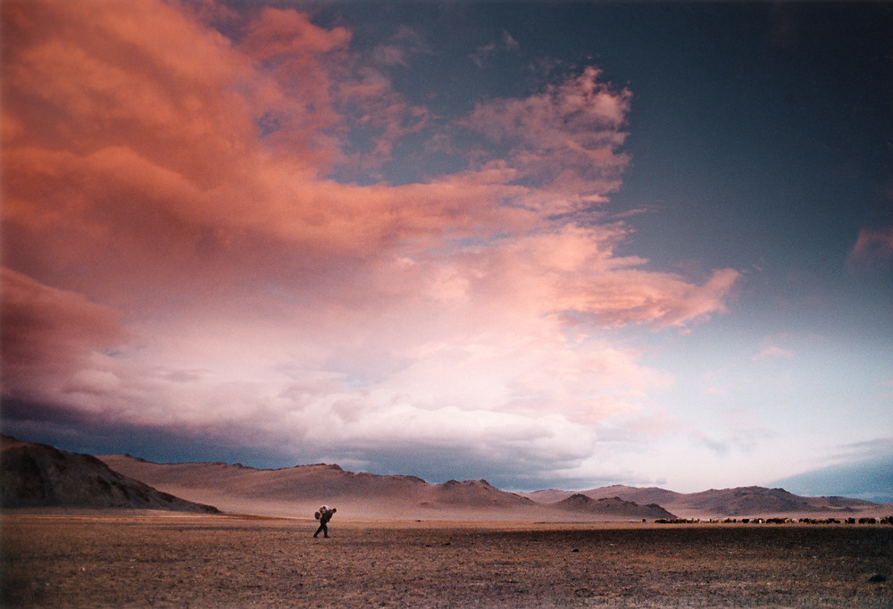 A traveller across Mongolia, carrying his backpack on his back, threatened by an upcoming storm, in the Province of Bayan Olgii, in Western Mongolia. Mongolia is a camper's paradise with no land-ownership, you can virtually camp anywhere, there are no restrictions.