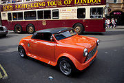 Small car with a very shallow roof passes a tall London tour bus in central London. This tiny Coupe is designed by Pininfarina.