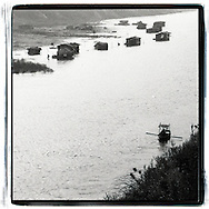 Small barge rows in direction of a floating village on the Red River, Hanoi, Vietnam, Southeast Asia