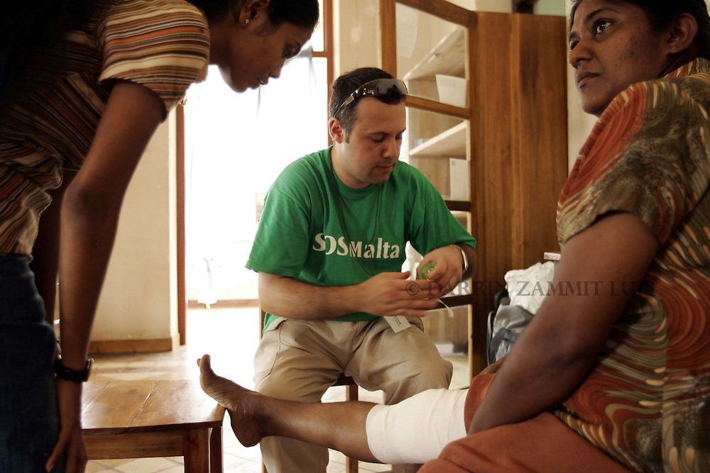 SOS Malta team leader David Grech (C) bandages a woman's leg at the SOS Malta clinic in Matara, on the south coast of Sri Lanka, on 14 January 2005..Photo by Darrin Zammit Lupi