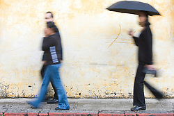 Woman with umbrella walking in front of colorful, painted wall, Antigua, Guatemala