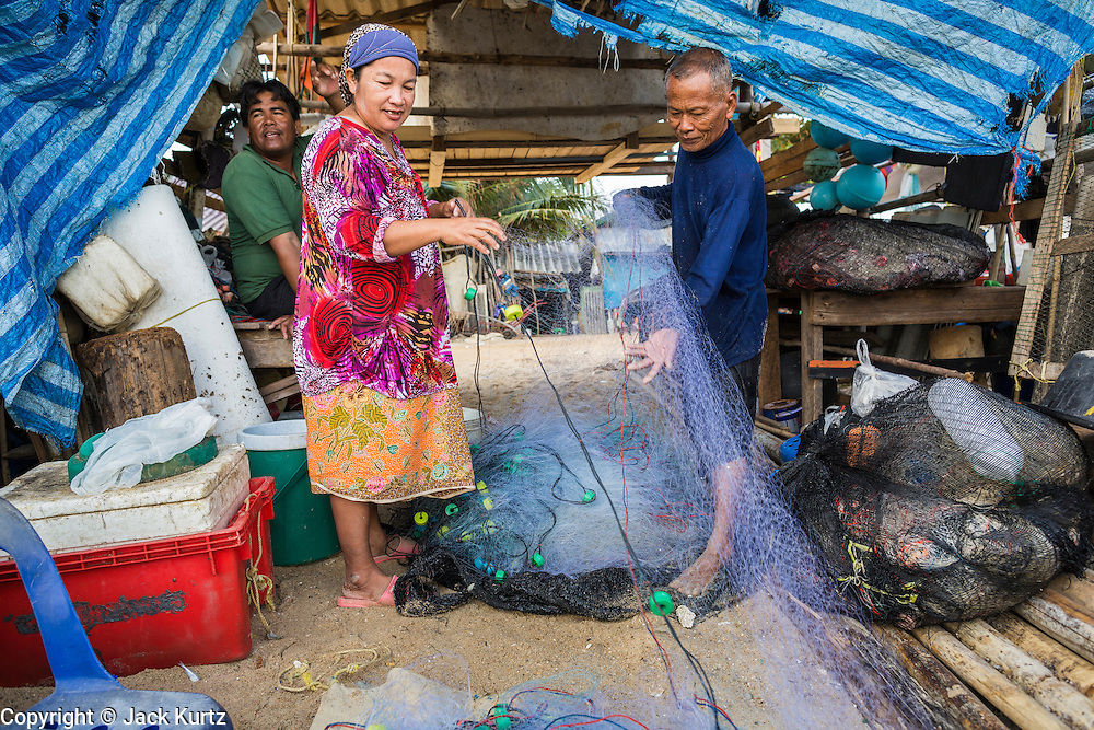 07 FEBRUARY 2014 - KAO SENG, SONGKHLA, THAILAND:  A fisherman and his wife sort out their nets in Kao Seng. Kao Seng is a traditional Muslim fishing village on the Gulf of Siam near the town of Songkhla, in the province of Songkhla. In general, their boats go about 4AM and come back in about 9AM. Sometimes the small boats are kept in port because of heavy seas or bad storms.     PHOTO BY JACK KURTZ