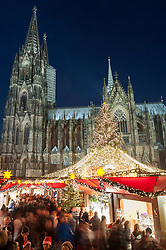 Busy Cologne Christmas Market beside the Cathedral at night in Germany