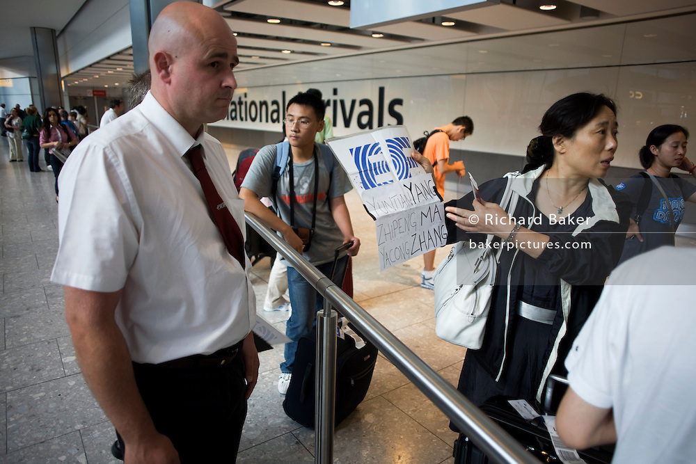 A greeting driver attempts to identify one of his passengers from a group of Chinese-speaking language students