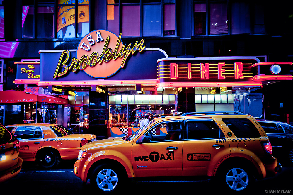 Taxis queue at dusk in Midtown Manhattan in front of the Brooklyn Diner.