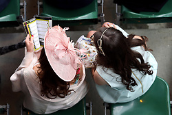 Female racegoers in the stands consult the race card during Grand National Day of the Crabbie's Grand National Festival at Aintree Racecourse, Liverpool.