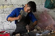 Joven llenando cohetones con pólvora. Al rellenar se debe compactar a presión. Se usa bronce y un martillo de plástico para evitar las chispas.
