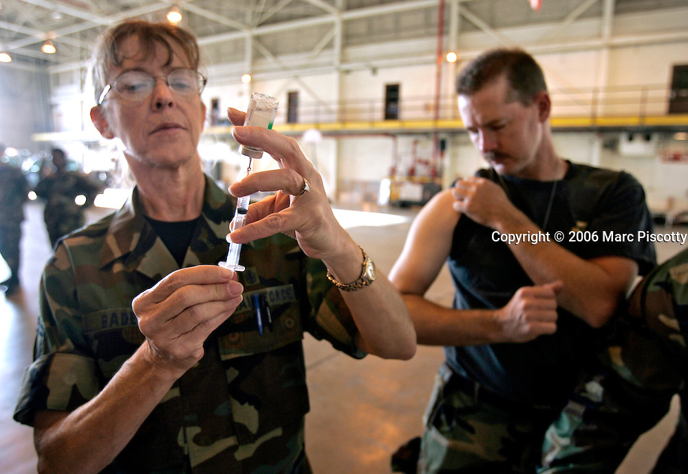 Air National Guard Senior Master Sargeant Linda Baden (left) of Aurora, Co. prepares a shot for Tech Sargeant Marc Fife (right) of Fort Collins, Co. as he prepares to leave for the Gulf Coast area Monday at Buckley Air Force Base. About 220 Colorado National Guard members left Buckley Air Force Base Monday September 5, 2005 to be deployed in a number of areas damaged by Hurricane Katrina recently. Members from an Army and Air Force National Guard units will be providing everything from security in the region to repairing infastructure to establishing tent cities for the evacuees. Baden said she was innoculating Air National Guard members for Typhoid, Hepatitis A and Tetanus..(MARC PISCOTTY / © 2005)