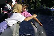 children pet captive bottlenose dolphins, Tursiops truncatus, in shallow petting pool at Sea World, Orlando, Florida