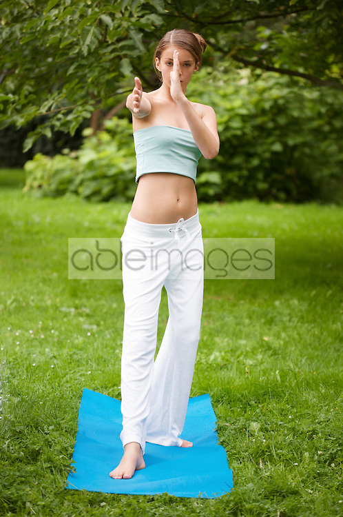 Young woman doing tai chi in the garden