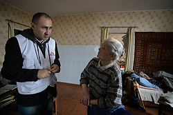 Doctor Kachatur Malakyan speaks to Valentina, 76 whohelps her husband, Nikolai, 77, take his medicine at their home in Debalseve. Nikola suffers from chronic cardia disease and is bed-ridden and relies on his wife to look after him.  MSF have recently begun a home visits project that sends teams of doctors and nurses into the community to deliver care to the hardest to reach patients.