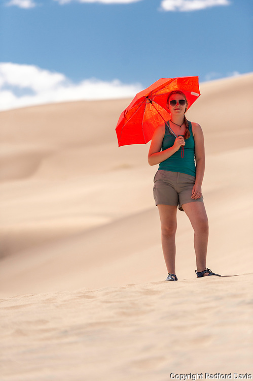 Woman with red umbrella, Great Sand Dunes National Park. Colorado.