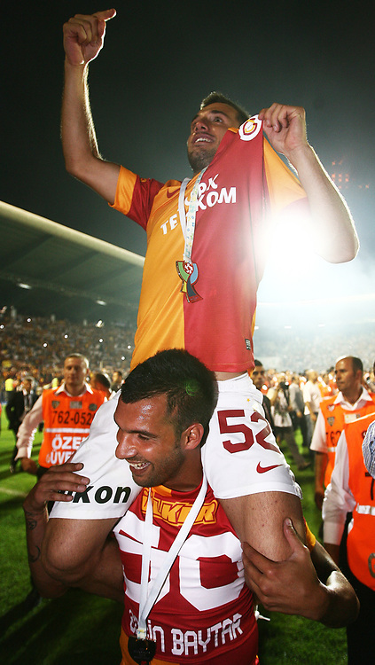 Galatasaray's players Engin Baytar and Emre Colak on celebrate with the trophy after their Turkish Super Cup 2012 soccer derby match Galatasaray between Fenerbahce at the Kazim Karabekir stadium in Erzurum Turkey on Sunday, 12 August 2012. Photo by TURKPIX