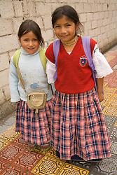 South America, Ecuador, Otavalo,  girls in school uniforms walking home from school