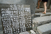 "A menu outside a home featuring traditional ""peasant"" dishes. Settlers from Shanxi Province founded the city over 500 years ago, mostly for the business opportunities that abounded on the ancient road from Shanxi Province to Beijing. Wayfarers needed places to stay and food to eat on their rigorous trek through the mountains. The town also served as a postal station. Under these conditions, Chuandixia flourished, even in its position near one of the most remote outposts of the Great Wall. ...."