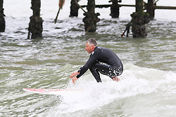 © Licensed to London News Pictures. 22/06/2015. Brighton, UK. A man is seen surfing close to Brighton Pier. Few people venture out on Brighton beach today as dark clouds loom over Brighton, today June 22nd 2015. Photo credit : Hugo Michiels/LNP