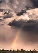 A rainbow forms as storm clouds break apart after a big rainfall.