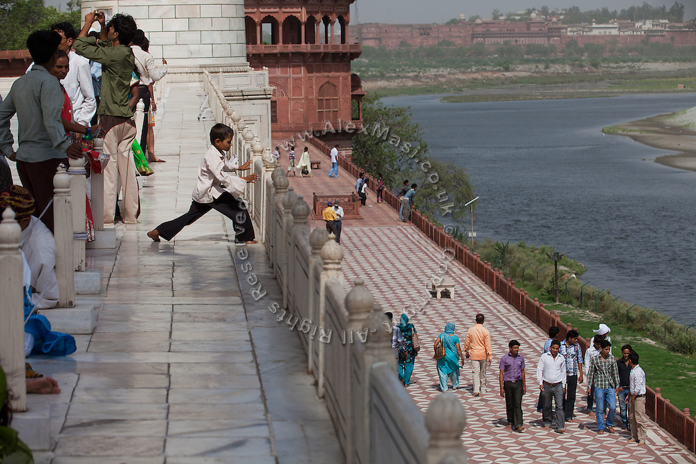 Visitors are looking at the heavily polluted and dry Yamuna River while standing inside the main complex of the Taj Mahal, in Agra. In the original design, there should be water on the right where people are walking, so as to prevent the Taj from falling towards the river.