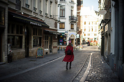 "© Licensed to London News Pictures. 23/11/2015. Brussels, Belgium. A woman walks down A deserted street at 2pm in central Brussels where the city is currently on ""lockdown"" amid ""imminent threat"" of Paris-style bomb and gun attacks. Photo credit: Ben Cawthra/LNP"
