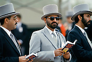 Arab racehorse owners in traditional top hats and tails watch the racing at Epsom Racecourse for Derby Day, UK