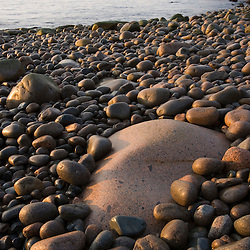 Early morning on the cobblestone beach in Momument Cove in Maine's Acadia National Park.  Otter Cliffs are in the distance.