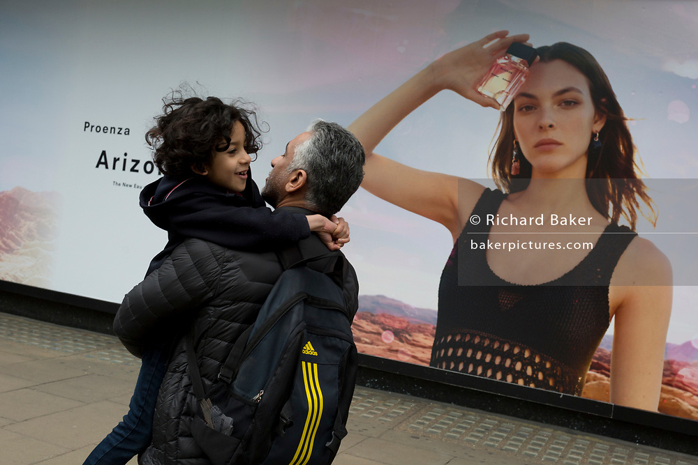 A man carries a child past a billboard ad featuring the face of a model advertising a perfume outside the retailer Debenhams on Oxford Street, on 16th April 2018, in London, England.