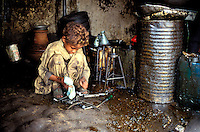 """Pakistan - """"Shiddis """", esclaves de l'empire des Indes - Province du Sind - Karachi -  Lyari, district surpeuplé du sud de Karachi abrite la plus forte concentration de Shiddis du Pakistan. Dans ce Harlem pakistanais, les Noirs prédominent surtout dans les ghettos pouilleux et malodorants de Baghdadi et Bombasa, quartiers à problèmes ravagés par la drogue, enclave où le taux de chômage peut atteindre 40 à 50%.- Tayyab, 8 ans, travaille dans un atelier de mecanique.<br /> // Pakistan, Shiddi, the black of Pakistan with African origine"""
