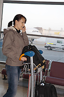 young woman arriving at the airport terminal calling on the phone