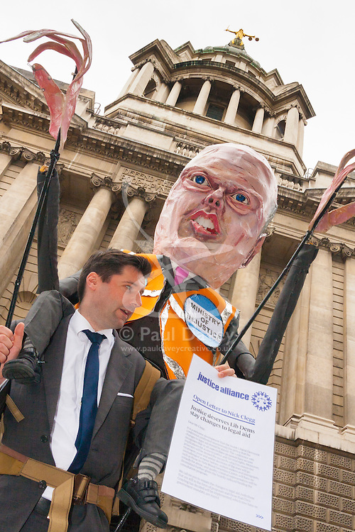 London, June 16th 2014. The statue of Lady Justice looks down from on top of the Old Bailey as Lawyers, students and barristers protest against Justice Minister Chris Grayling's cuts to legal aid budgets.
