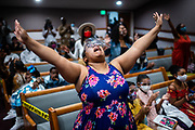 """Victoria """"Nicole"""" Samuels, 35, of Sacramento, raises her hands in praise during a service at St. Paul Missionary Baptist Church in Oak Park in Sacramento on Easter Sunday on April 4, 2021. The Easter Sunday service was the church's first service indoors since coronavirus related closures in March 2020."""