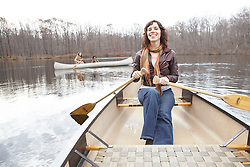 Lifestyle image of smiling woman paddling boat in lake during late autumn