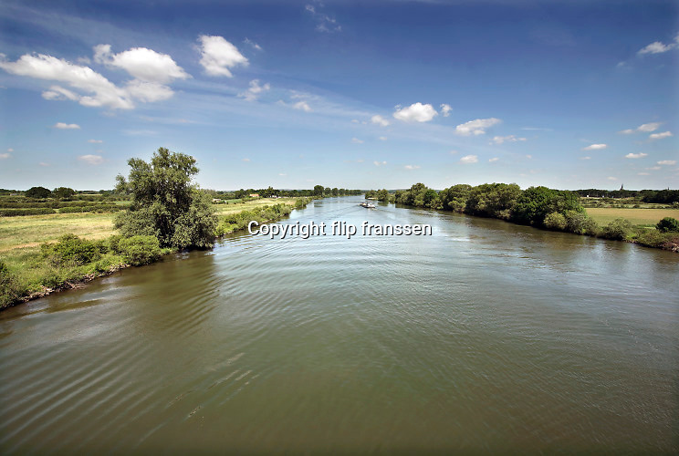 Nederland, Gennep, 29-5-2020  De Maas in noord limburg . Deze rivier wordt vanf Maastricht via sluizen stuwen op peil gehouden en heeft daardoor geen natuurlijk laagwater . Bij onvoldoende aanvoer van water vanuit Belgie wordt er minder geschut om water te sparen en moeten schepen soms lang wachten om de sluis door te kunnen . Staatsbosbeheer en rijkswaterstaat leggen natuurgebieden aan in de uiterwaarden van de grote rivieren . Natuurontwikkeling in de uiterwaarden en rivierverruimende projecten voor een betere afvoer van het water bij hoogwater . Hier is bijvoorbeeld het natuurgebied maasheggen, een oud cultuurlandschap waarbij heggen percelen afbakenen .Foto: Flip Franssen