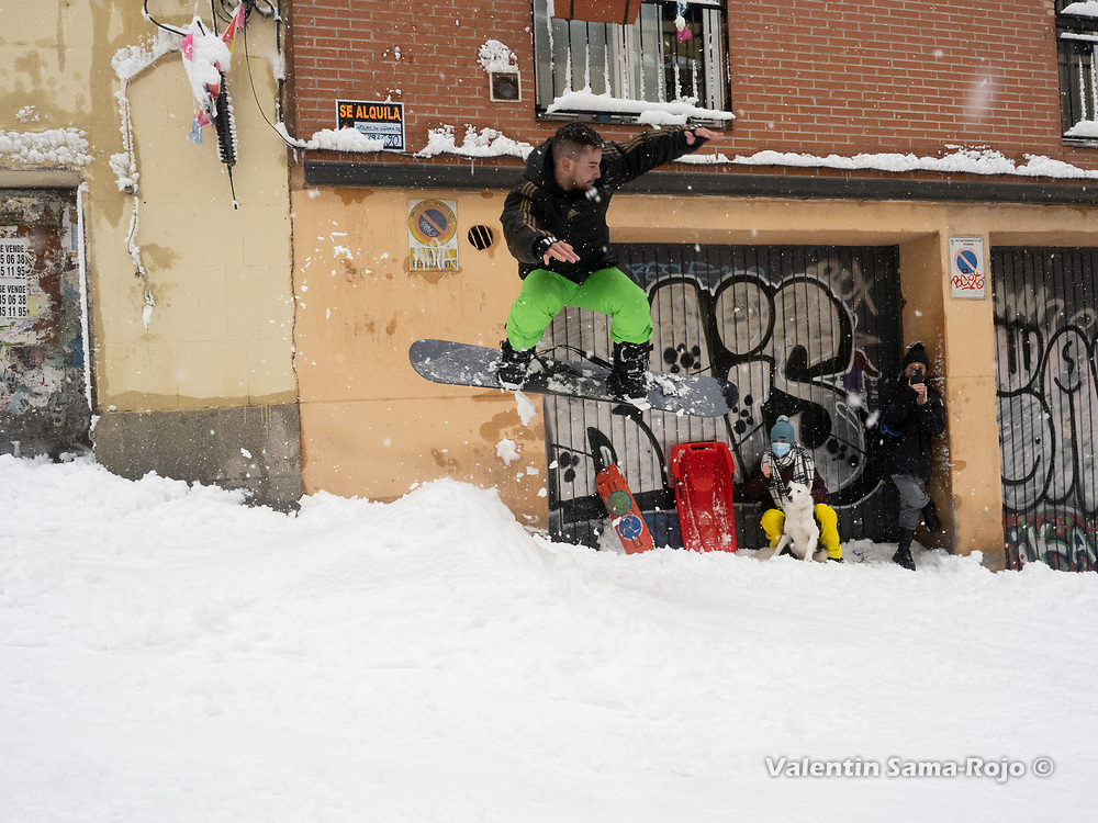 Madrid, Spain. 9 th January, 2021. A man jumpig with a snowboard on a street of Madrid's downtown. Storm Filomena hits Madrid (Spain), a weather alert was issued for cold temperatures and heavy snow storms across Spain; according to the weather agency Aemet is expected to be one of the snowiest days in recent years. © Valentin Sama-Rojo.