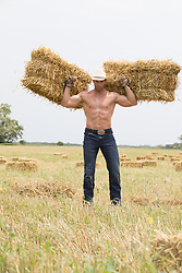 strong muscular cowboy holding two hay bales on his shoulders