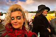 Glastonbury Festival, 2015. Shangri La is a festival of contemporary performing arts held each year within Glastonbury Festival. The theme for the 2015 Shangri La was Protest. The morning after; woman at dawn in front of the Hell stage.