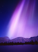 Purple and blue aurora above the Talkeetna Mountains and Coolorado Lake with subtle blue light of the approaching dawn, geomagnetic storm on March 31, 2001, Broad Pass, Alaska.