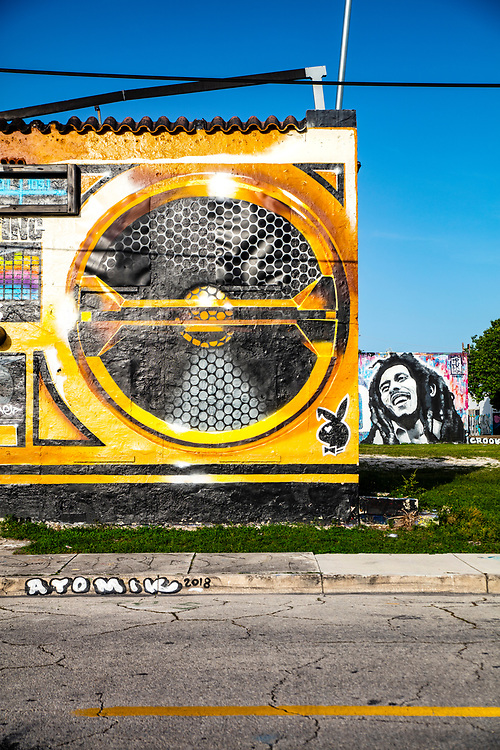 In 2010 an Argentine street artist named Sonni painted an abandoned Wynwood building to resemble a boombox.<br /> <br /> But someone painted an advertisement over the two-story tall artwork.<br /> <br /> So, in 2012, Miami street artist, Trek6, and San Francisco-based artist Chor Boogie, reimagined The Boombox Building with a different design -- shown in an earlier image in this online gallery.<br /> <br /> A few years later the building -- by now a beloved local landmark -- was repainted again, in the version shown here.<br /> <br /> In the background is a mural portrait of reggae star Bob Marley.