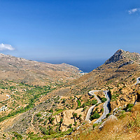 Naxos. Cyclades. Greece. The scenic north-east coast of Naxos and its mountainous landscape with the stunning backdrop of the blue sky and waters of the Mediterranean Sea just outside the pretty northern coastal village of Apollonas.