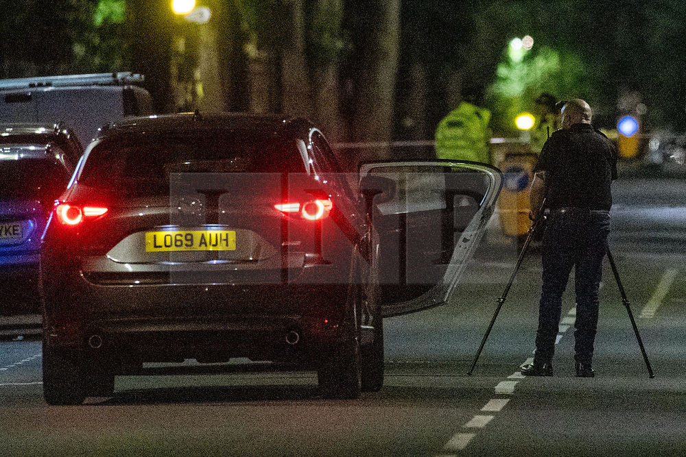 © Licensed to London News Pictures. 26/06/2020. London, UK. A forensic investigator take a photograph of a vehicle inside the police cordon. A person has been stabbed on Du Cane Road in East Acton on Thursday 25th June 2020. A cordon closed off a large section of the road underneath a railway bridge where two vehicles remained. Photo credit: Peter Manning/LNP